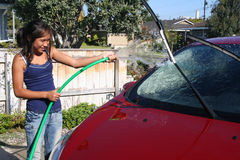Car Wash. Girl outside washing her red car Royalty Free Stock Photos