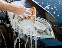 Car wash. Car Hand Wash with Yellow Sponge and Soap Royalty Free Stock Photography