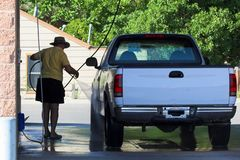 Car Wash. An elderly man is s proud new owner of a pickup at a car wash royalty free stock photos
