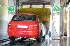 Car wash. Red car covered in shampoo is washed inside automatic car wash Royalty Free Stock Photo