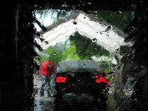 Car wash. Back of car going through a car-wash seen though wet windshield stock photography