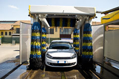 Car wash in action. White car wash with soap and yellow and blu brushes Royalty Free Stock Images