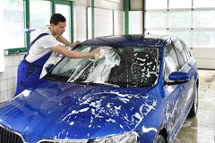 car wash as service/ after-sales service by mechanics in a garage/ car dealership stock images