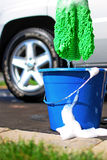 Car Wash Bucket. Image of some of a soap bucket and wash tool with car in the background Royalty Free Stock Photos