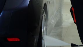 Car wash. Car washer washes the car. A car wash worker washes a car with water. Close-up. stock video footage