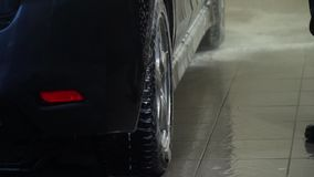 Car wash. Car washer washes the car. The car washer washes the foam out of the car. Close-up. stock footage