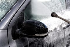 Car at the car wash. A car is cleaned at the car wash with water and a brush Royalty Free Stock Images