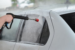 Car Wash Closeup. Washing white modern Car by High Pressure washer. Royalty Free Stock Photography