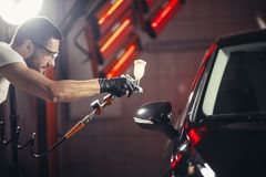 Car wash and coating business with ceramic coating.Spraying varnish to car. Man wear protective mask and eyewear at work. Automobile industry. Car wash and Stock Photo