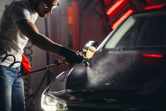 Car wash and coating business with ceramic coating.Spraying varnish to car. Staff wear protective mask and eyewear at work.Car Care Business. Automobile royalty free stock photos