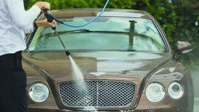 Car wash employee servicing expensive business class auto, using water spray gun stock video footage