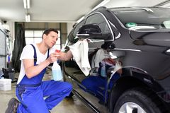 Car wash - employees of a car dealership clean a vehicle profess stock image