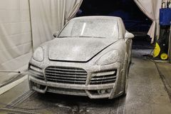 7 March, 2017, Ukraine, Kiev. Car wash. Wash the car. The car is in the foam. Porsche Cayenne royalty free stock photography