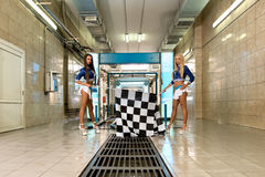 Car wash. Leggy girls posing with checkered flags Royalty Free Stock Photos