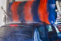 Car wash, rotating red and blue brushe. Royalty Free Stock Images