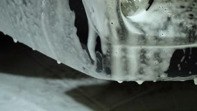 Car wash. Car washer washes the car. The car is covered with white washing foam. Close-up. stock footage
