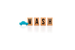 Car Wash - wooden block letters on white reflective background w. Ith blue wooden car shape Stock Image