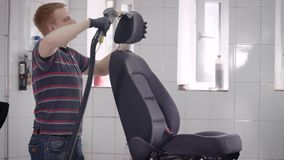 Car wash worker is cleaning seat of automobile in a room, using vacuum cleaner, seat is standing on rack. In centre of garage stock footage