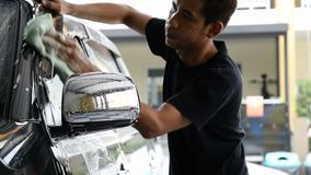 Car care center industry. Car wash worker wearing a T-shirt is using a sponge to clean the car in the car wash center, concept for car care industry stock footage
