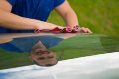 Car wash worker, wipes the car with a red rag with mappings Stock Photography
