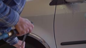 The car is washed with high-pressure water at a car wash close-up.  stock footage
