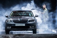 A man with a beard or car washer washes a gray car with a high-pressure washer at night in a shop wash royalty free stock images