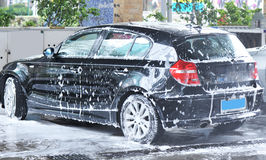 Car washing. Washing black car with bubbles Stock Images