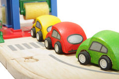Car washing. Cue of toy wooden coloured cars to washing station Stock Image
