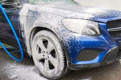 Car washing. Cleaning car using high pressure water. Machine in foam royalty free stock images