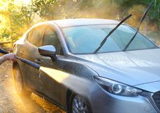 Car Washing. Cleaning grey color car using high pressure water. In the morning with sunray stock photography
