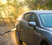 Car Washing. Cleaning grey color car using high pressure water. In the morning with sunray royalty free stock images