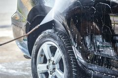 Car washing. Cleaning car with high pressure water and foam.  royalty free stock photo