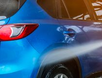 Car washing with high pressure water. Car care service business. Concept. Back view of blue compact SUV car with sport and modern design are cleaning in car Royalty Free Stock Images