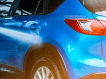Car washing with high pressure water. Car care service business. Concept. Back view of blue compact SUV car with sport and modern design are cleaning in car Stock Photo