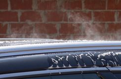Car washing with hot steam. Outdoor with brick wall in the background stock photo