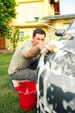 Car washing. Male cleaning car using sponge and foam. In the house yard Royalty Free Stock Photo