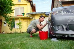 Car washing. Man cleaning his car using sponge and foam Stock Photography
