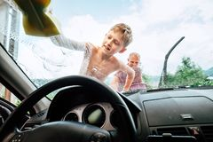Car washing process: son helps his father to wash a car front wi. Ndow Royalty Free Stock Image