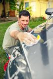 Car washing. Male cleaning car using sponge and foam. Car washing. Smiling male cleaning car using sponge and foam in the house yard Royalty Free Stock Photos