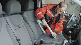 Worker clean cabin of car with vacuum cleaner. Car washman cleans the interior of automobile. Worker uses vacuum cleaner to clean the cabin of car from dirty stock footage