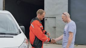 Car washman gives key from car to customer after washing his car. Car washman comes to the auto outdoors. The owner of car comes to the worker and people shakes stock video footage
