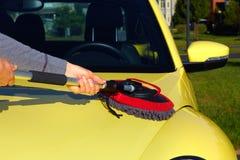 Car with wax and polish brush. Hand with brush washing a car. Waxing and polishing Royalty Free Stock Image