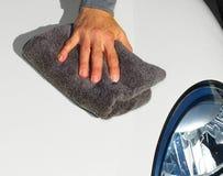 Car with wax and polish cloth. Hand with cloth washing a car. Waxing and polishing Stock Photo