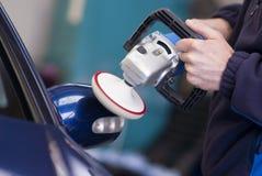 Car wax on wing mirror using rotary buffer. Man using rotary buffer on vehicle wing mirror Stock Photos