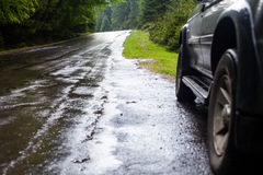 Car and wet road in summer forest. Wet road after rain and car standing on the roadside in the forest Royalty Free Stock Image