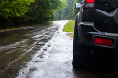 Car and wet road in summer forest. Wet road after rain and car standing on the roadside in the forest Royalty Free Stock Images