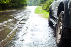 Car and wet road in summer forest. Wet road after rain and car standing on the roadside in the forest Stock Images