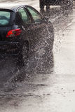 Car on a wet street at heavy rain Stock Photo