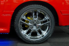 Car wheel. Close-up of car wheel and red car Royalty Free Stock Images