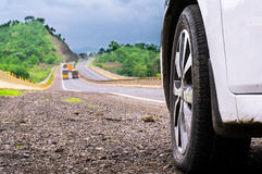 Car wheel against hilly road with trees Stock Image